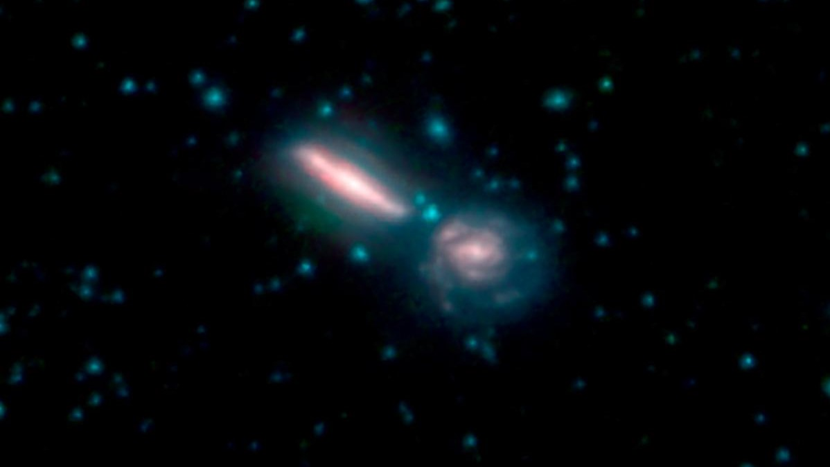 This photo shows two merging galaxies known as Arp 302, also called VV 340. In these images, different colors correspond to different wavelengths of infrared light. Blue and green are wavelengths both strongly emitted by stars. Red is a wavelength mostly emitted by dust. Photo and Caption Credit: NASA/JPL-Caltech