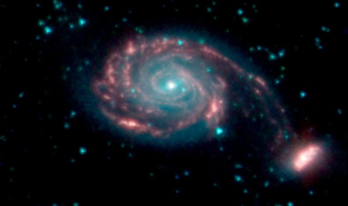 The larger NGC 7752 galaxy and smaller NGC 7753, collectively called Apr86, are in the process of merging. The different colors correspond to different wavelengths of infrared light. Blue and green are wavelengths both strongly emitted by stars. Red is a wavelength mostly emitted by dust. Image Credit: NASA/JPL-Caltech