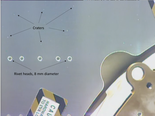 A size comparison of the impacts compared to rivet heads on the Columbus module. Photo Credit: ESA/NASA