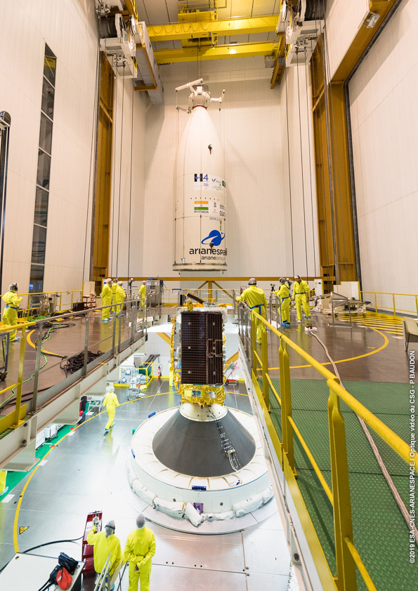 Saudi Geostationary Satellite 1/Hellas Sat 4, inside the payload fairing in the background, is being readied to be placed over the GSAT-31 co-passenger in advance of launch. Photo Credit: Arianespace