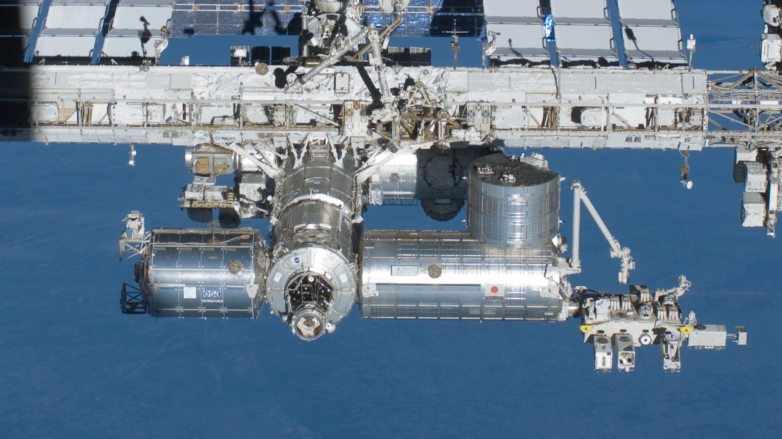 """The European Space Agency's Columbus module, lower left, has been in space for more than 10 years and has sustained """"hundreds"""" of debris impacts. Photo Credit: NASA"""