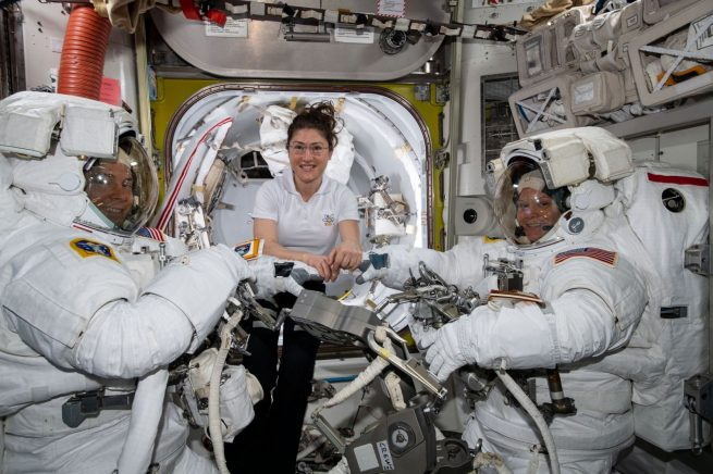 Nick Hague, left, and Anne McClain, right, are assisted in their spacesuits by Christina Koch for their March 22, 2019, spacewalk. Photo Credit: NASA