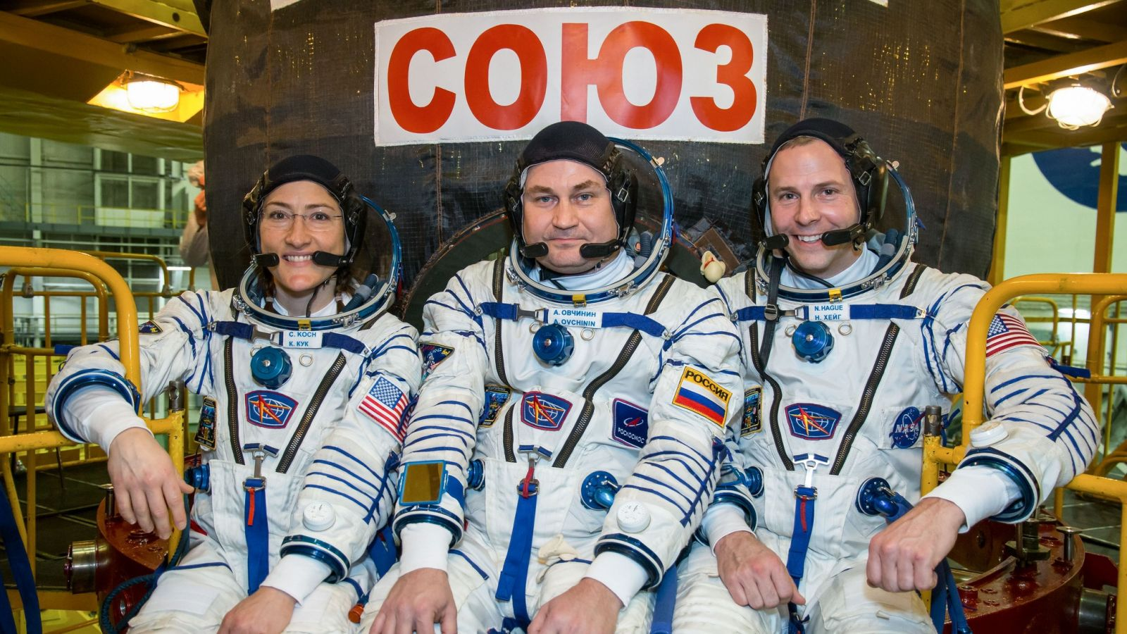 NASA astronaut Christina Koch, left, Russian cosmonaut Aleksey Ovchinin, center, and NASA astronaut Nick Hague stand pose for a photo in front of their Soyuz MS-12. Photo Credit: NASA
