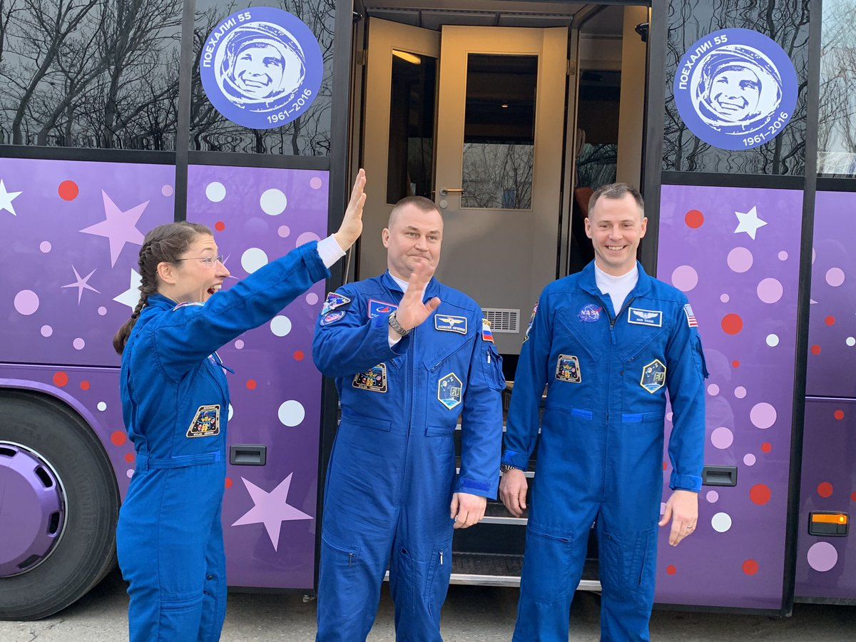 Koch, left, Ovchinin, center, and Hague wave goodbye to friends and colleagues before heading to the launch complex to suit up and enter the Soyuz rocket for their flight to the ISS. Photo Credit: NASA/Roscosmos