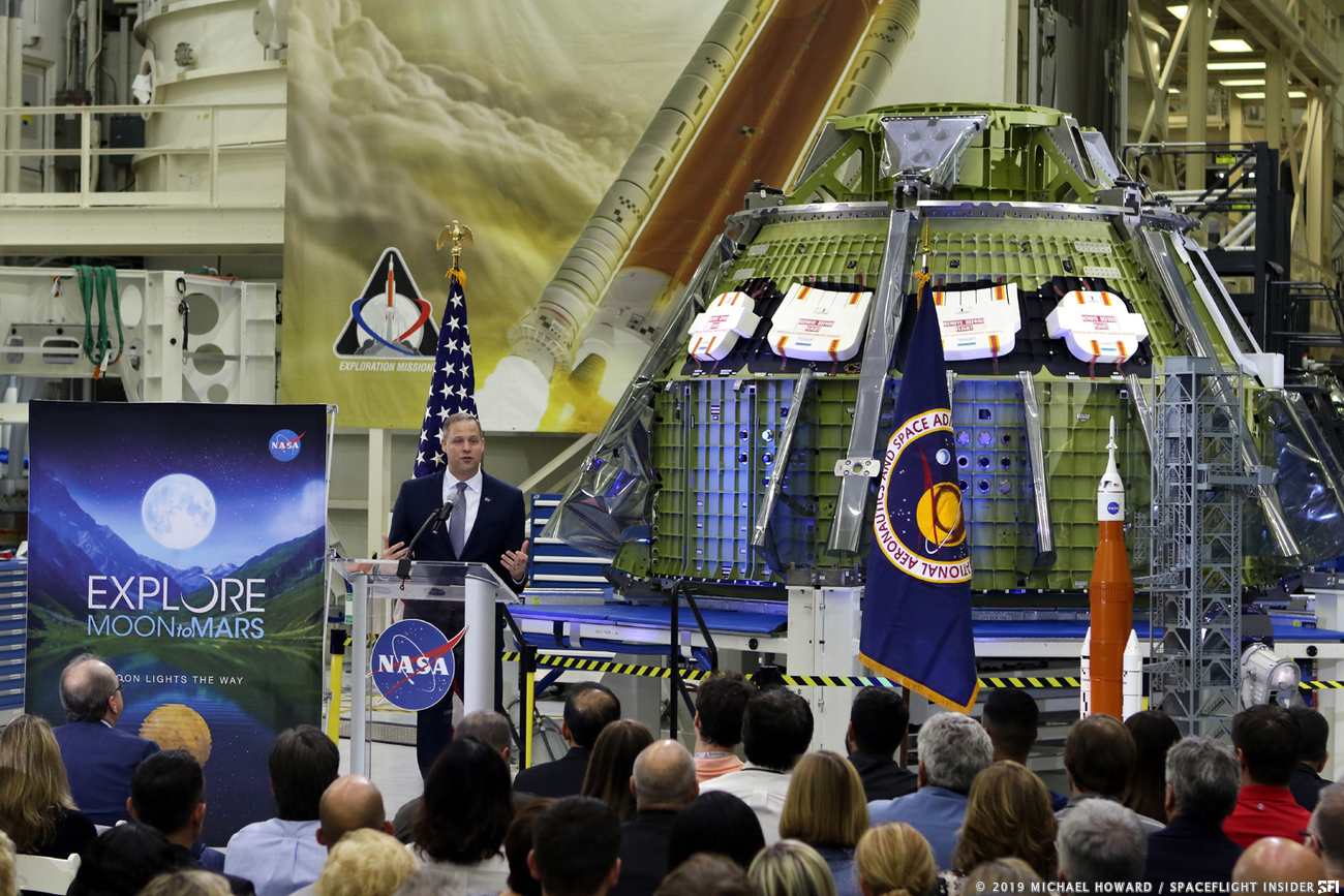 NASA Administrator Jim Bridenstine talks about the FY 2020 budget proposal for the space agency during a speech at Kennedy Space Center. Behind him was the pressure vessel for Orion's Exploration Mission 2, slated for a crewed 2022 flight around the Moon. Photo Credit: Michael Howard / SpaceFlight Insider
