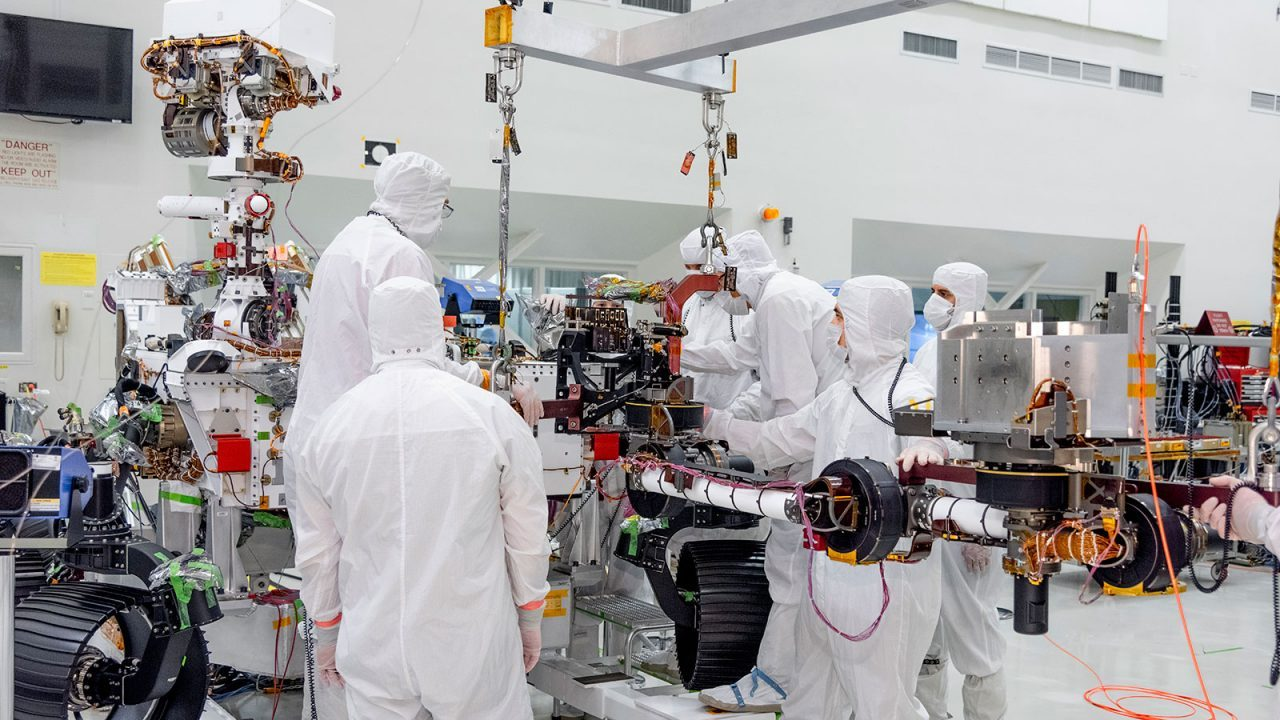 On June 21, 2019, engineers at NASA's Jet Propulsion Laboratory install the main robotic arm on the Mars 2020 rover. Measuring 7 feet (2.1 meters) long, the arm will allow the rover to work as a human geologist would: by holding and using science tools with its turret. Photo Credit: NASA/JPL-Caltech