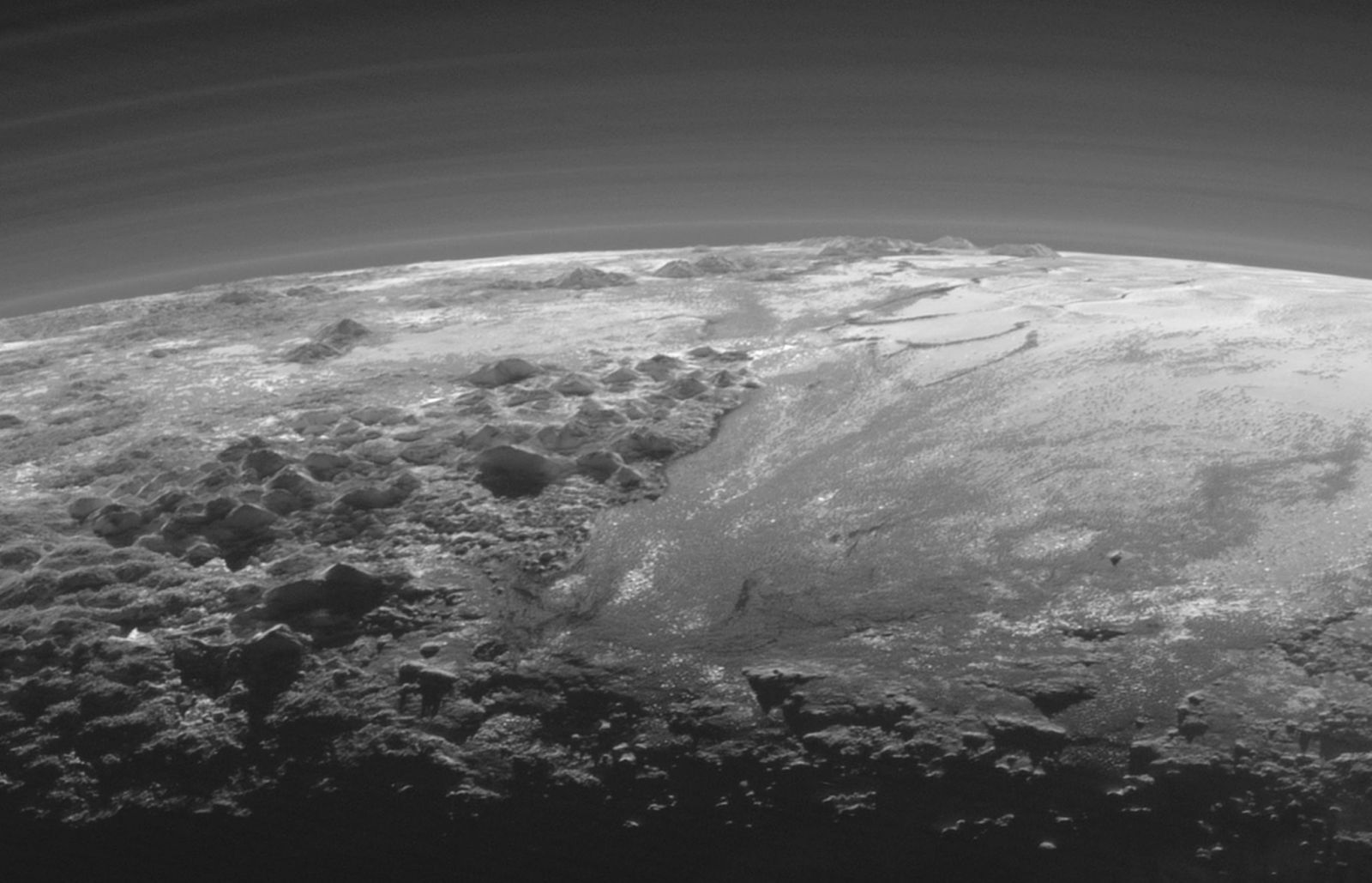 Look back image of Pluto's atmospheric hazes, surface ice mountains, and plains, taken 15 minutes after closet approach. Image Credit: NASA/JHUAPL/SwRI