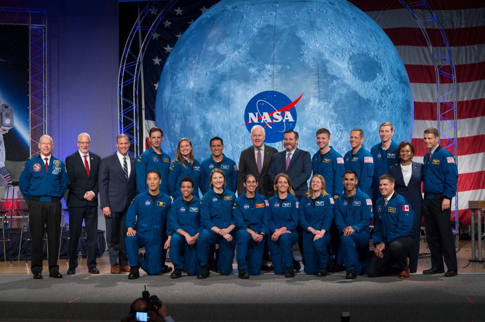 NASA's new class of astronauts – the first to graduate since the agency announced its Artemis program – appear on stage during their graduation ceremony at the agency's Johnson Space Center in Houston on Jan. 10, 2020. The class includes 11 NASA candidates, as well as two Canadian Space Agency (CSA) candidates, selected in 2017. They will join the active astronaut corps, beginning careers in exploration that may take them to the International Space Station, on missions to the Moon under the Artemis program, or someday, Mars. Pictured from left are: Kayla Barron of NASA, Zena Cardman of NASA, Raja Chari of NASA, Matthew Dominick of NASA, Bob Hines of NASA, Warren Hoburg of NASA, Jonny Kim of NASA, Joshua Kutryk of CSA, Jasmin Moghbeli of NASA, Loral O'Hara of NASA, Jessica Watkins of NASA, Jennifer Sidey-Gibbons of CSA, and Frank Rubio of NASA. Photo and Caption Credit: NASA