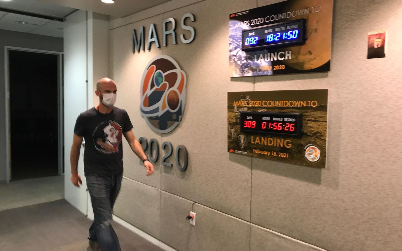 Ian Clark walks past mission countdown clocks in the Perseverance offices at JPL. Clark was needed on-Lab to supervise the assembly and cleaning of the sample tubes that will hold Martian sediment and rock. Photo Credit: NASA/JPL-Caltech