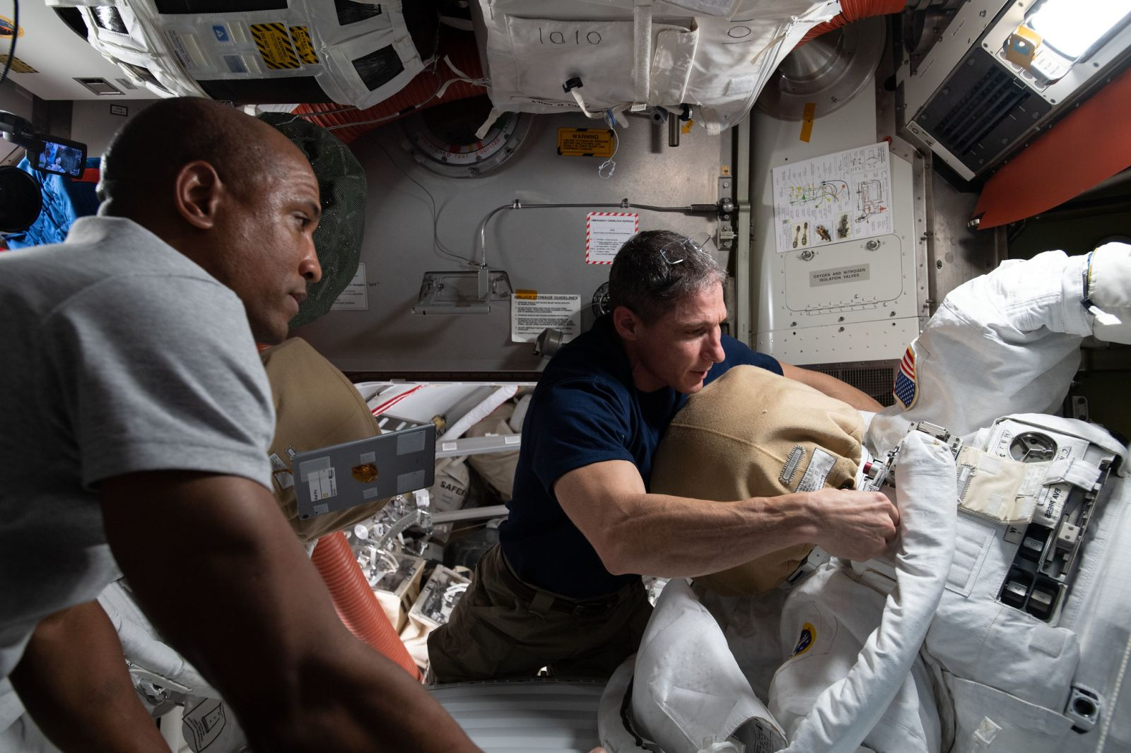 NASA astronauts Victor Glover, left, and Mike Hopkins work to ready their spacesuits in advance of their extravehicular activities. Credit: NASA