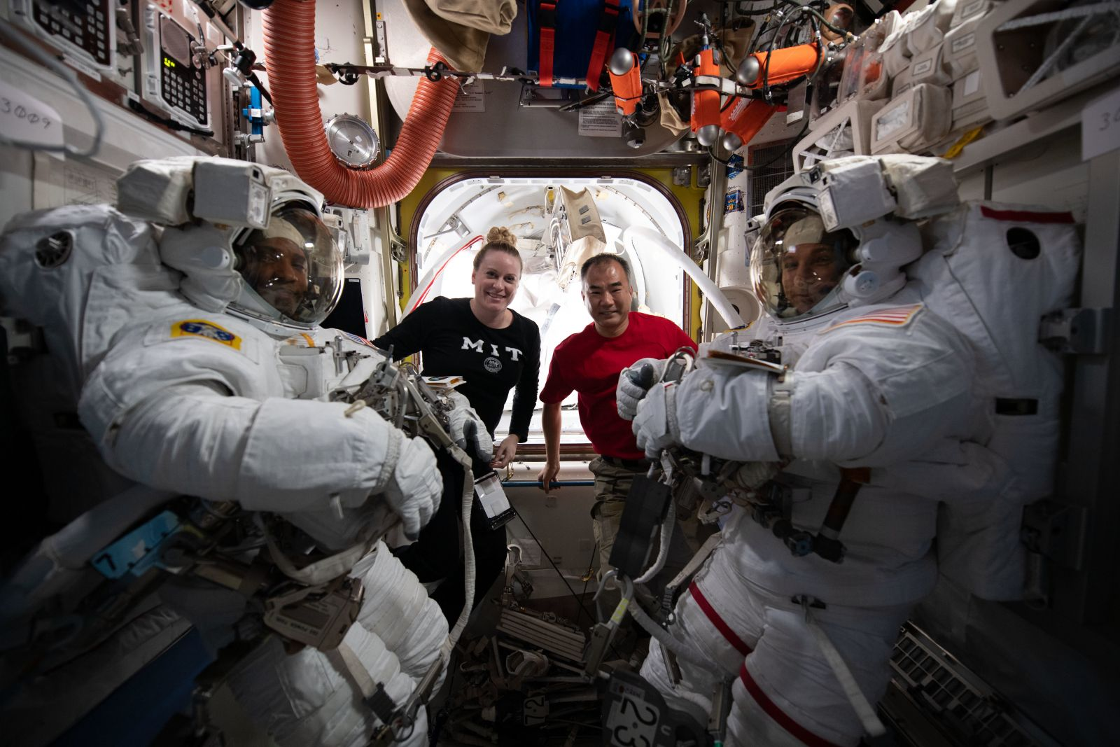NASA astronaut Mike Hopkins right and Victor Glover right seen in their spacesuits before the first spacewalk of 2021. NASA astronaut Kate Rubins in the black shirt worked with Japanese astronaut Soichi Noguchi in the red shirt assisted the spacew