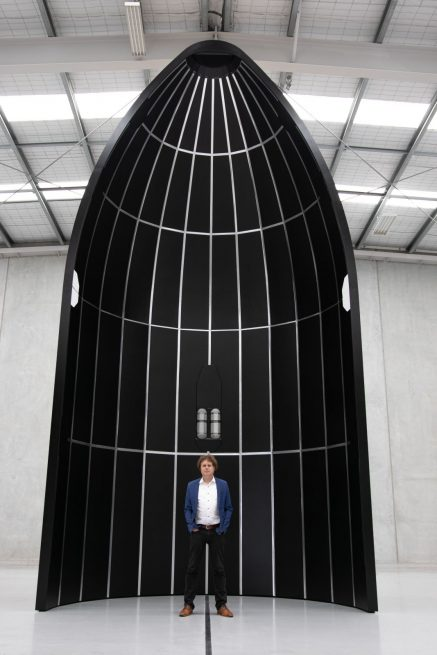 Rocket Lab CEO Peter Beck stands inside a mockup of one of the payload fairing halves that'll be used for its Neutron rocket. Credit: Rocket Lab