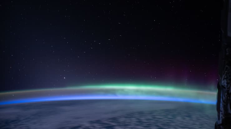 A view of several Starlink satellites as seen from the International Space Station. They are seen as a string of blurred dots going from the Earth on the lower left part of the image to the upper center part of the image. Credit: NASA