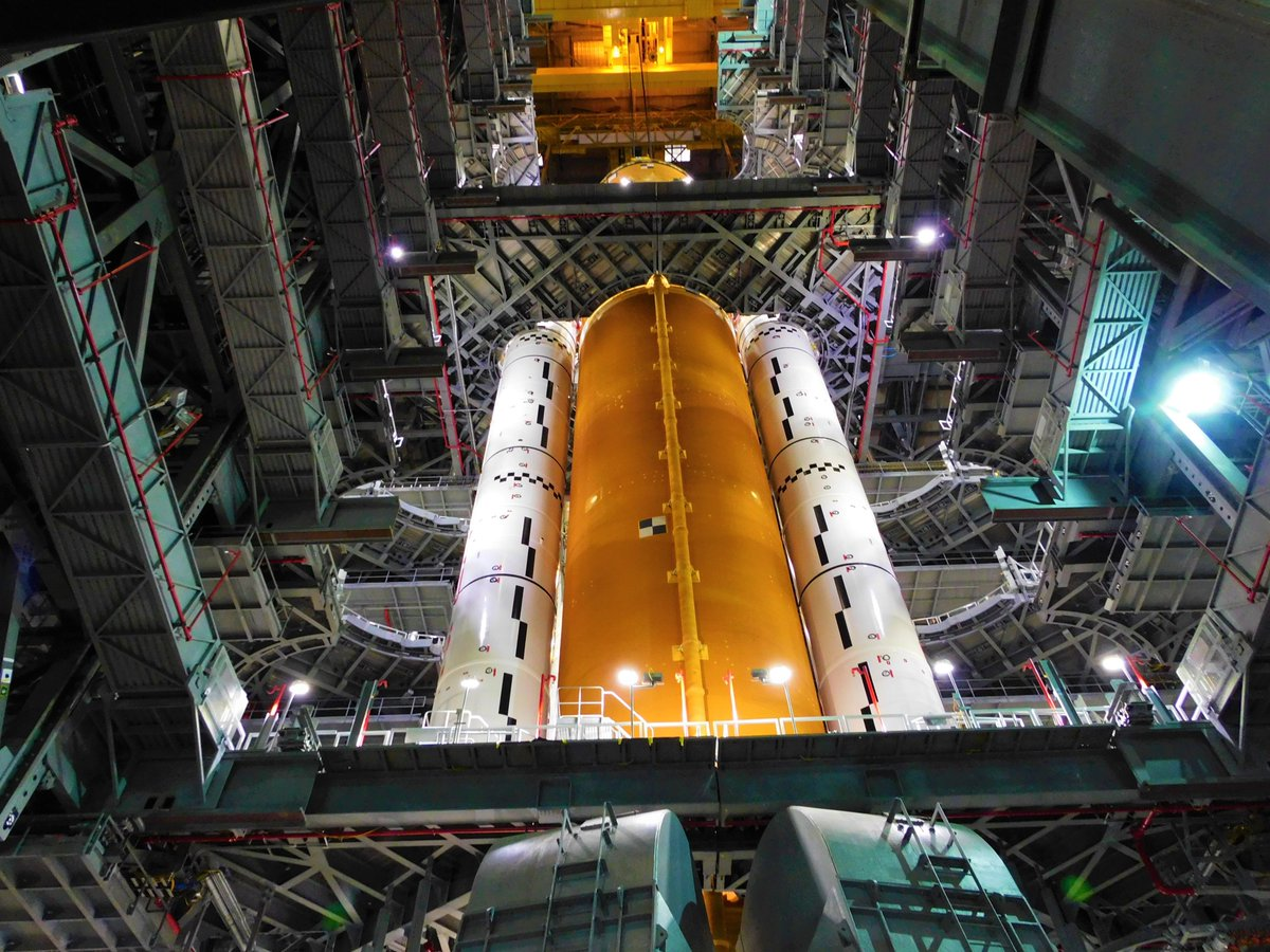 The first core stage fore NASA's Space Launch System is lowered between the two five-segment solid rocket boosters that have already been assembled on the mobile launcher in the Vehicle Assembly Building's High Bay 3. Credit: NASA