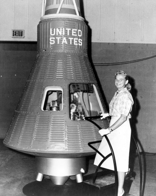 """Jerrie Cobb, one of the """"Mercury 13"""" Women in Space candidates, stands next to a Mercury capsule. Credit: NASA"""