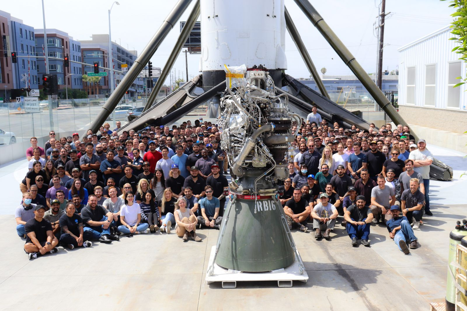 SpaceX employees pose around the 100th build of a Raptor engine at the company's factory in Hawthorne, California. Credit: SpaceX