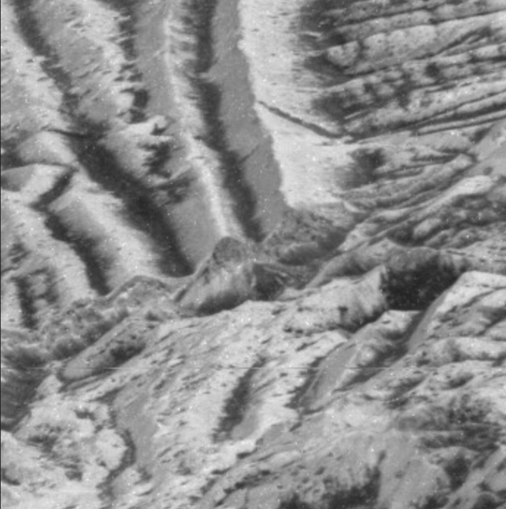 This enlarged photo, captured by the Galileo spacecraft, shows bright cliffs at the top and areas that have undergone impact gardening below them. Credit: NASA/JPL-Caltech
