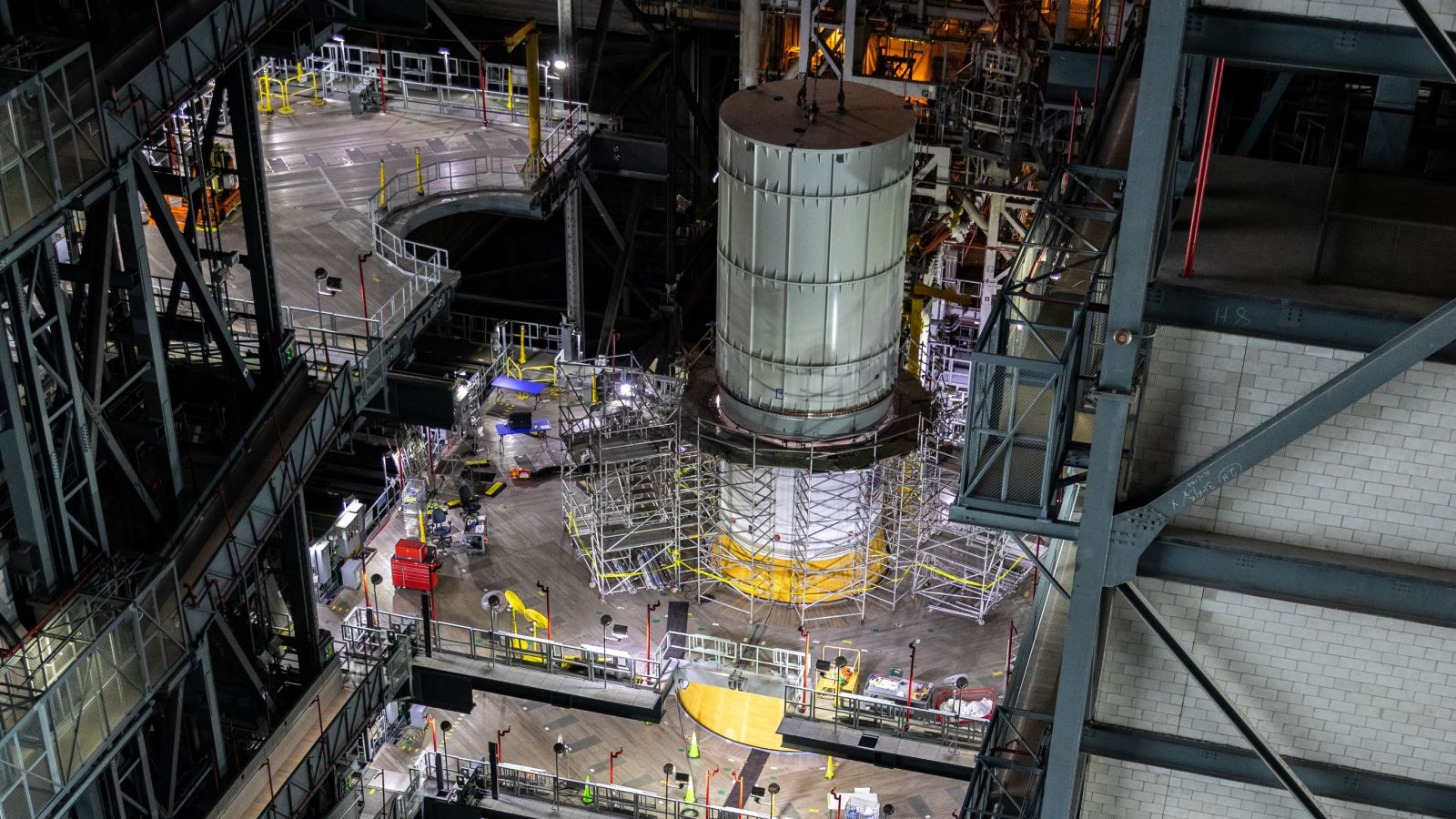 An Orion mass simulator sits atop the stacked Space Launch System while NASA engineers prepare to perform vibrational tests on the rocket. Credit: NASA