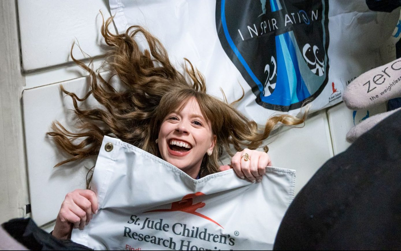 Hayley Arceneaux floats in a zero-g plane while holding a banner for St. Jude Children's Research Hospital. Credit: Inspiration4 / John Kraus